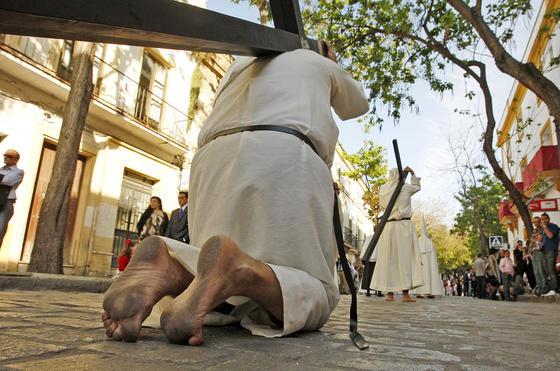 Cruces de penitencia y rodillas al suelo. Dura penitencia la de este nazareno de la hermandad del Transporte.  Foto: juan carlos toro