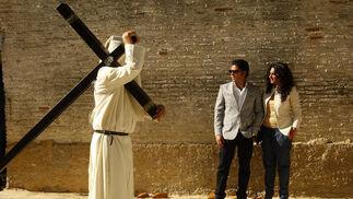 Un penitente pasa junto a una pareja que contempla el discurrir de la hermandad.  Foto: Juan Carlos Toro