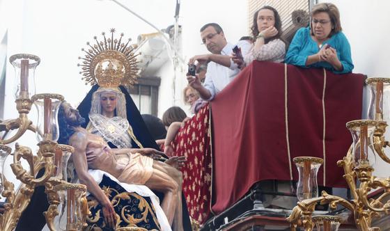 Un hombre toma una fotografía a la Virgen de Las Angustias desde un balcón durante los primeros momentos de la estación de penitencia.  Foto: vanesa lobo