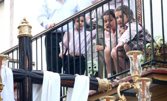 Una niña intenta tocar desde un balcón la cruz del paso de Nuestra Señora de Las Angustias.  Foto: vanesa lobo
