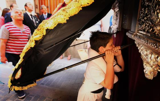 Un niño, ya tocado por el arte costalero, observa a sus mayores bajo el mismísimo manto de la Virgen de la Paz en su Mayor Aflicción.  Foto: miguel ángel gonzález