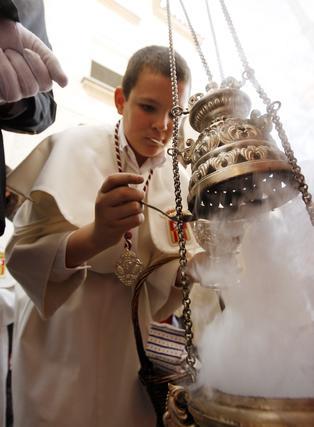 El monaguillo vierte con profusión incienso en el incensario.  Foto: Juan Carlos Toro