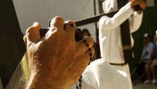 penitencia. Un nazareno del Transporte reza el Rosario con una cruz de penitencia sobre sus hombros.  Foto: Juan Carlos Toro