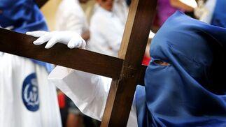 Un penitente de la hermandad de la Borriquita porta una cruz tras el paso de misterio.  Foto: Pascual