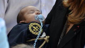 Un pequeño monaguillo de la hermandad del Perdón duerme sobre los brazos de un familiar.  Foto: manuel aranda