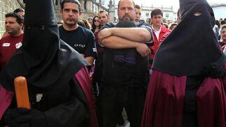 ostaleros del Cristo de la Viga aguardan tras el paso el momento de ponerse bajo las trabajaderas.  Foto: Miguel Ángel González