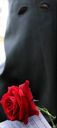 Un nazareno, con la rosa que llevaría a sus pies el Cristo  Foto: Miguel Ángel González