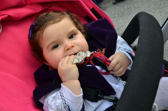 Una guapa monaguilla muerde la medalla de la hermandad.  Foto: Manuel Aranda