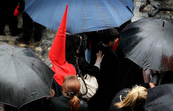 Un nazareno de la Hermandad del Desconsuelo se abre paso entre las personas que, con paraguas, aún esperaban que Los Judíos se hicieran a la calle.  Foto: Miguel Ángel González