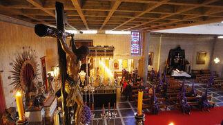 Hermanos de la Defensión oran en el interior del templo de Capuchinos. En primer término, el misterio y, al fondo, el palio de la O.  Foto: Juan Carlos Toro