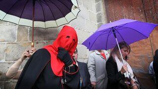 Un nazareno de Los Judíos pasa bajo un paraguas en las inmediaciones de la iglesia de San Mateo.  Foto: Miguel Ángel González