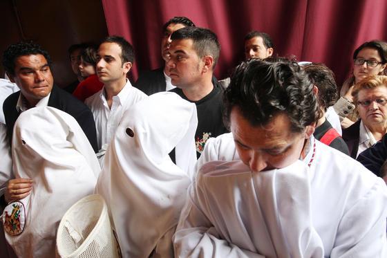 Nazarenos de San Benito se lamentan ante el frontal del paso de la cofradía.  Foto: Vanesa Lobo