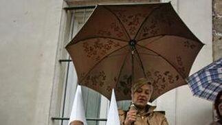 La señora y los niños, paraguas en mano, esperan el desenlace ante la capilla del Cristo del Amor.  Foto: Pascual