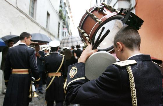 Un joven músico utiliza su tambor para protegerse de la lluvia.  Foto: Pascual