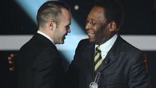 Pele entrega a Iniesta el distintivo que lo incluye en el once ideal del año. / AFP