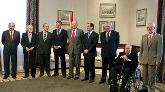 El rey Juan Carlos posa con Miguel Roca (i), Santiago Carrillo (2i), Landelino Lavilla (3i), José Luis Rodríguez Zapatero (4i), José Bono (4d), Felipe González (3d), Manuel Fraga (en silla de ruedas) y Alejandro Rojas Marcos (d), momentos antes del almuerzo que compartió en el Congreso de los Diputados con los principales líderes políticos que se encontraban en el Congreso en el intento del golpe de Estado el 23-F. / EFE