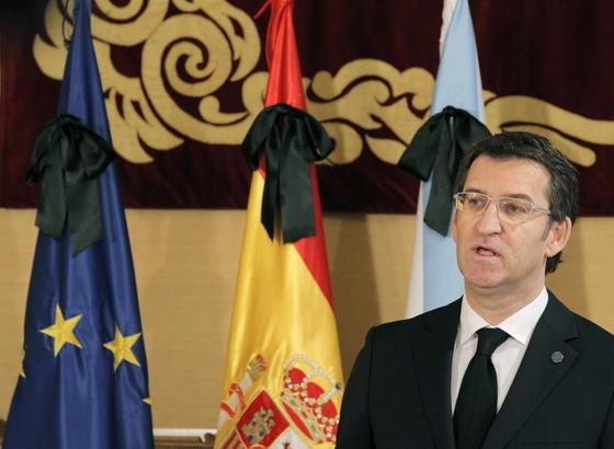 Alberto Núñez Feijoó, con las banderas europea, española y gallega ataviadas con crespones negros en señal de luto por la muerte de Manuel Fraga. / EFE