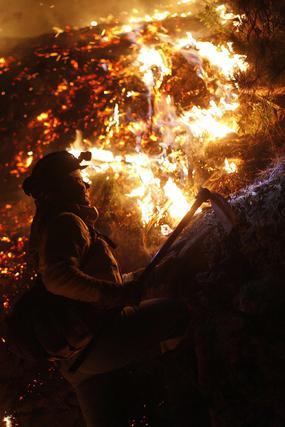 Dantesca imagen entre llamas, anoche  Foto: Jon Nazca / Reuters