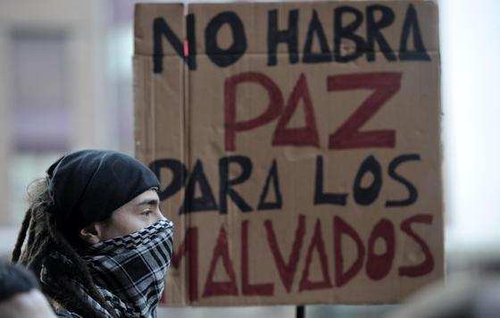 Un joven delante de una pancarta en la movilización de Valencia.  Foto: efe/afp/reuters