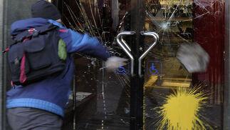 Un joven lanza piedras y bolas de pintura contra un banco.  Foto: Afp