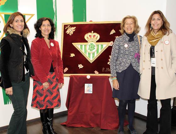 Tania Halcón de la Lastra, Olga Tassara, Consuelo Candau y Nieves de la Calle, voluntarias de Andex, junto al tapiz donado por Pilar Mencos a la asociación para su venta.  Foto: Victoria Ramírez