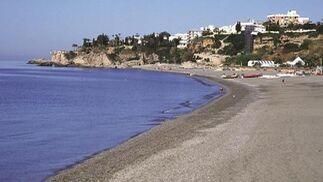 2. Burriana (Nerja)  Numerosas urbanizaciones de casitas con jardín, ubicadas sobre escarpadas rocas, rodean esta extensa playa que es, sin lugar a dudas, la más conocida y turística de la costa nerjeña. Cuenta, además, con el distintivo Q de calidad turística, marca que representa la calidad en el sector turístico español, así como la Bandera Azul de la Unión Europea. El acceso principal es a la salida de Nerja en dirección Almería en la N-340, y a la derecha, a la altura de la urbanización Verano Azul. La playa está totalmente equipada y suele ser frecuentada por familias. El entorno es diverso y desde sus 800 metros de longitud se divisan montañas y acantilados. Se puede practicar windsurf, vela y submarinismo y jugar al voley.   Foto: Turismo Costa del Sol