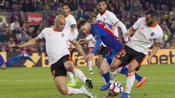 Messi trata de salir de la presión de tres rivales.