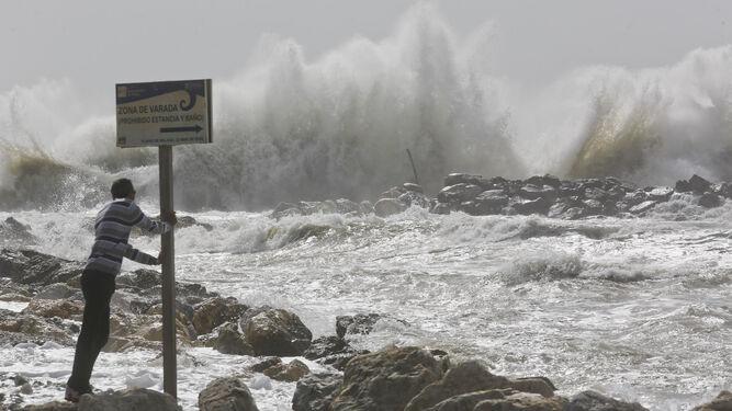 Un joven observa en primera línea el intenso oleaje en la playa de Sacaba Beach de la capital.