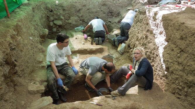 El equipo de arqueólogos e historiadores trabajando en otra fosa de Álora.