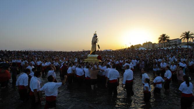 La Virgen del Carmen de El Palo, ante cientos de malagueños en el momento de su embarque.