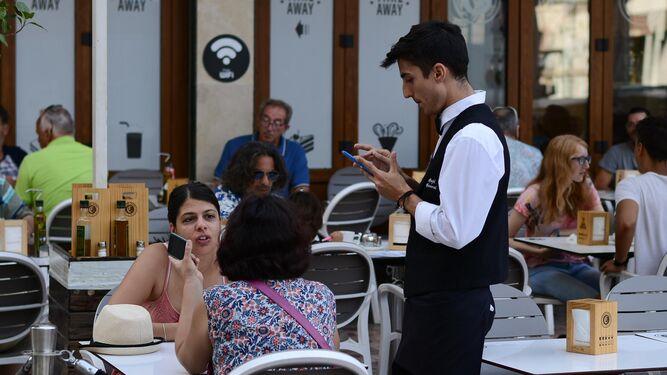 Un joven camarero sirve a dos clientas en una de las terrazas del centro de Málaga.