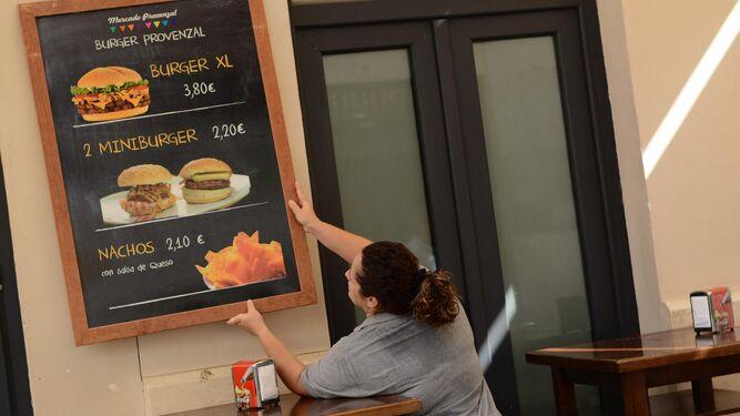 Una empleada coloca un cartel en un restaurante de Málaga.