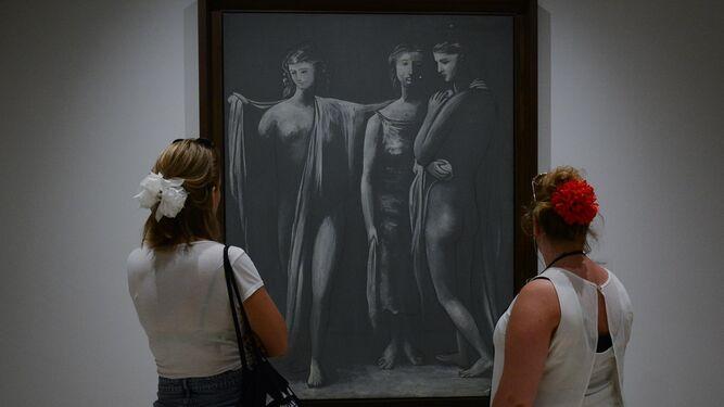 Dos mujeres con una flor de feria en el pelo observan un cuadro de la colección del Museo Picasso.