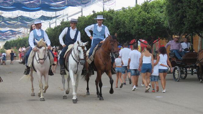 Un grupo de jinetes y una familia pasean por una de las calles del Recinto Ferial.