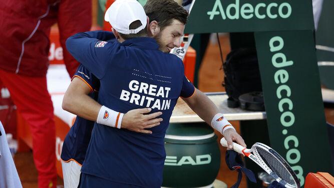 El británico Cameron Norrie es abrazado por su capitán Leon Smith tras ganar a Roberto Bautista.