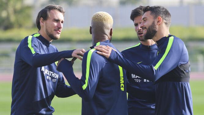 Ignasi Miquel, Adrián y Borja Bastón, rodeando a Brown Ideye en un entrenamiento.