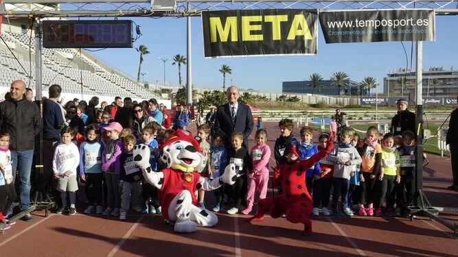 El alcalde posa junto a un grupo de niños en la línea de meta.