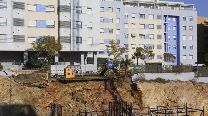 Vista general del hueco de la obra y de cómo ha afectado al parque infantil y a una parte de la entrada del garaje de la urbanización anexa.