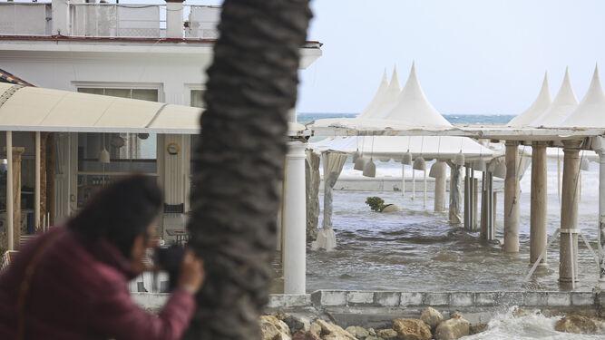 Una persona hace una foto del local anegado por el agua.