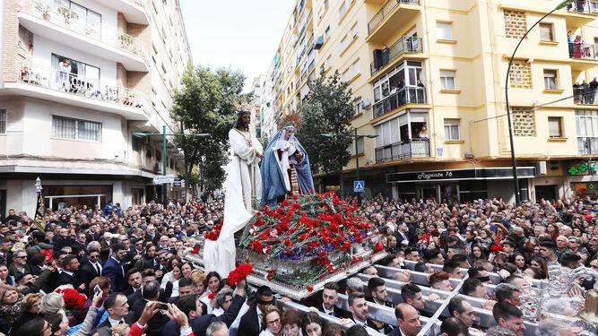 Las imágenes discurren por el barrio de La Trinidad mientras depositan claveles en el trono.