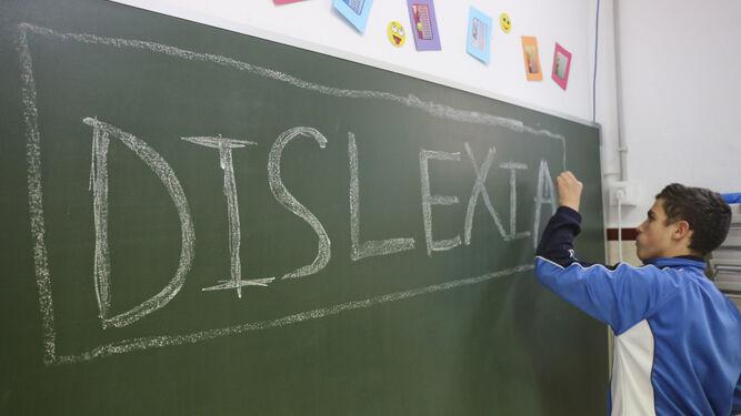 Antonio, alumno del colegio La Goleta con dislexia, escribe en la pizarra de un aula.