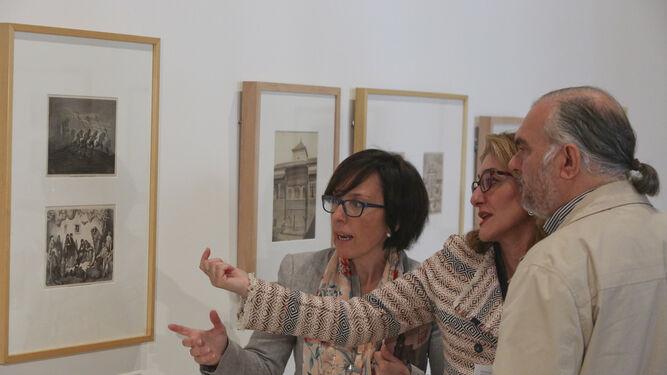Nuria García, Lourdes Moreno y Juan Antonio Fernández Rivero discuten sobre una de las estampas.