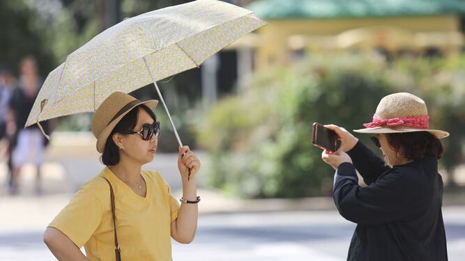 Una turista, ayer, se cubre del sol.