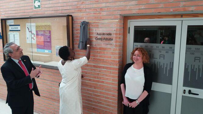 Caddy Adzuba revela la placa con su nombre en la facultad junto al rector de la UMA, José Ángel Narváez; y la decana del centro, Inmaculada del Postigo.
