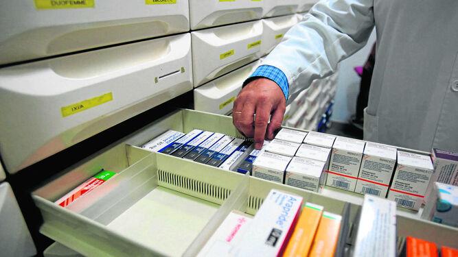 Un farmacéutico busca medicamentos en su botica. 707a2f8d6d4