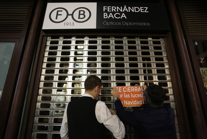 Un camarero ayuda a Manolo a colocar el cartel de cerrado en la joyería Fernández Baca.